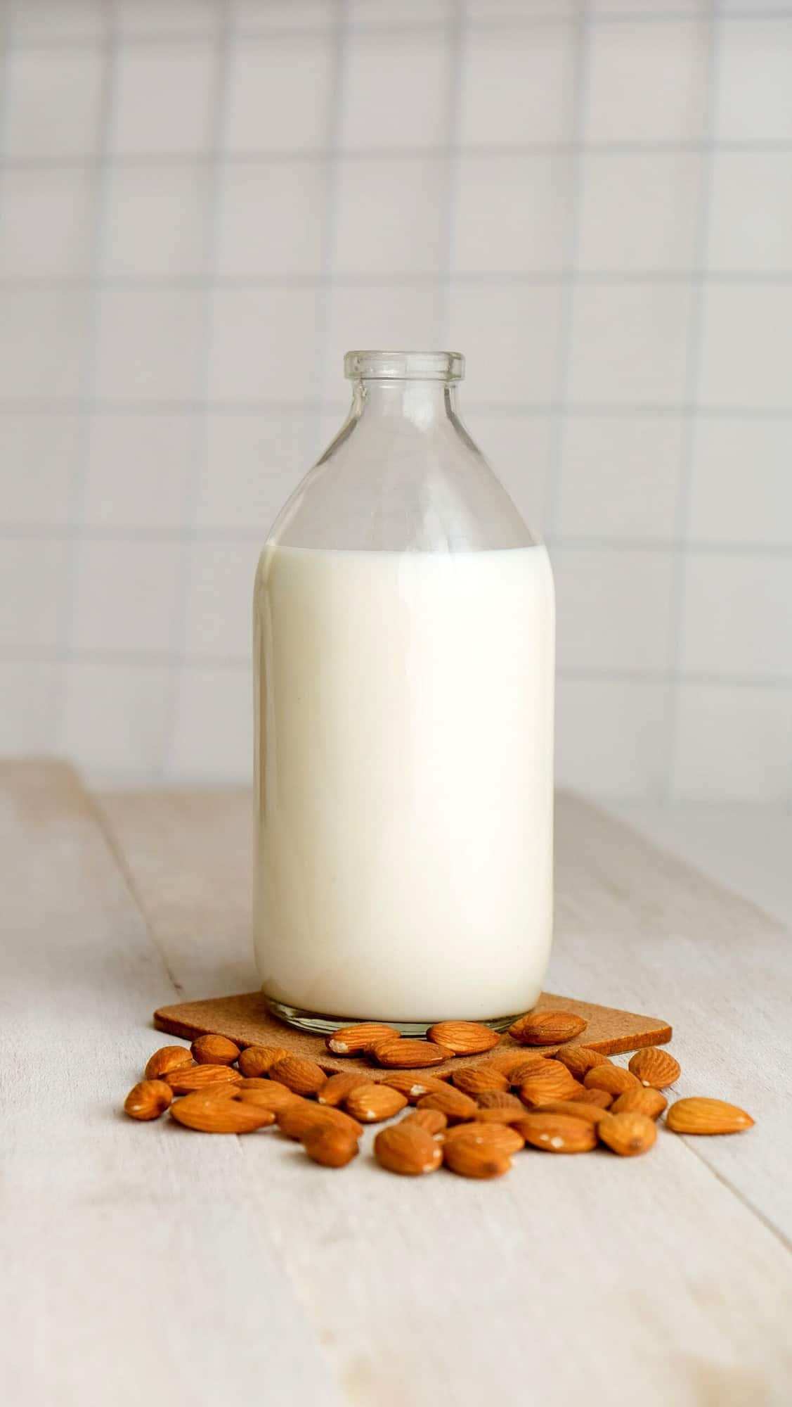 A bottle of almond milk with almonds scattered around it.