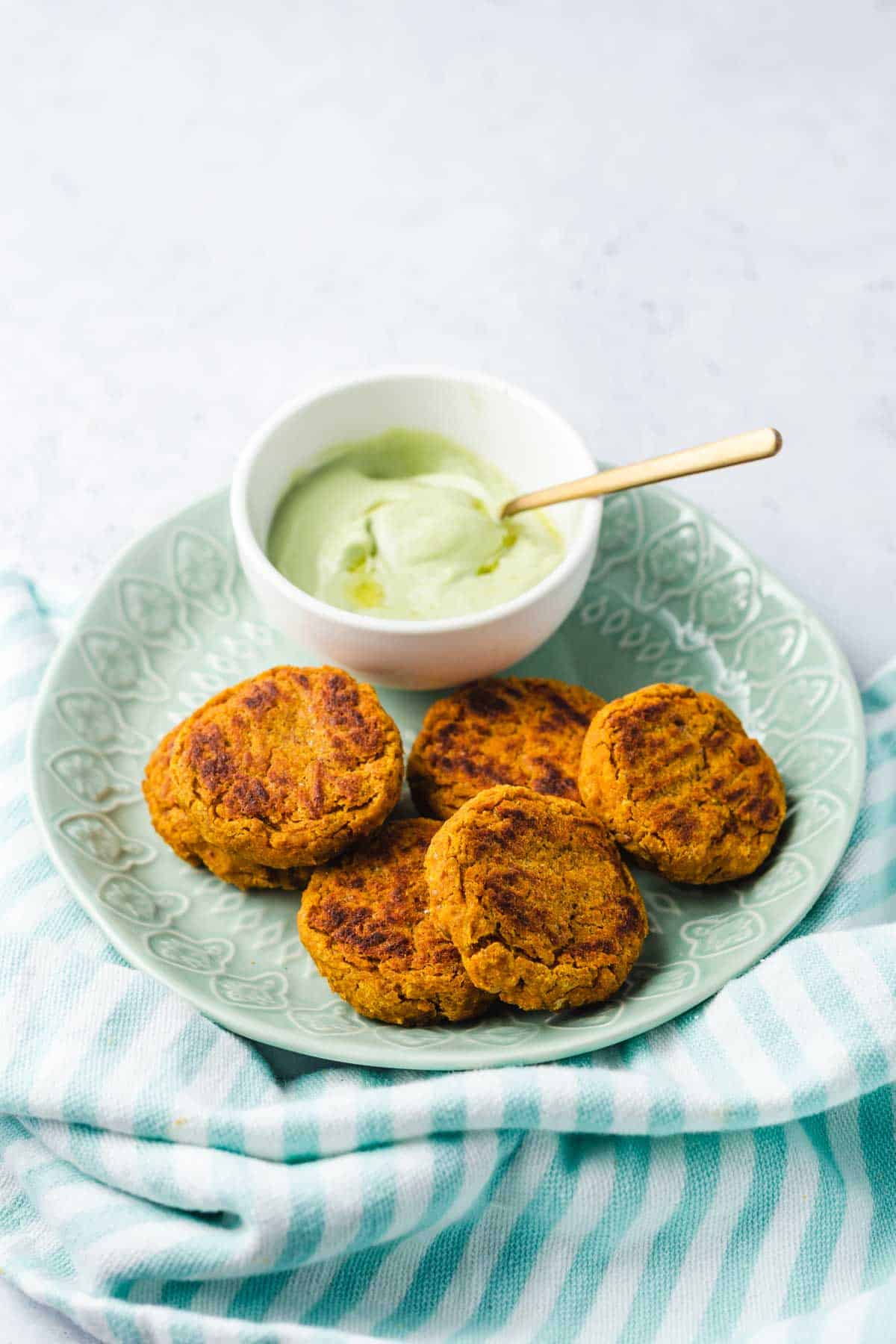 Close up image of sweet potato chickpea patties on a green plate served with avocado sauce on the side.