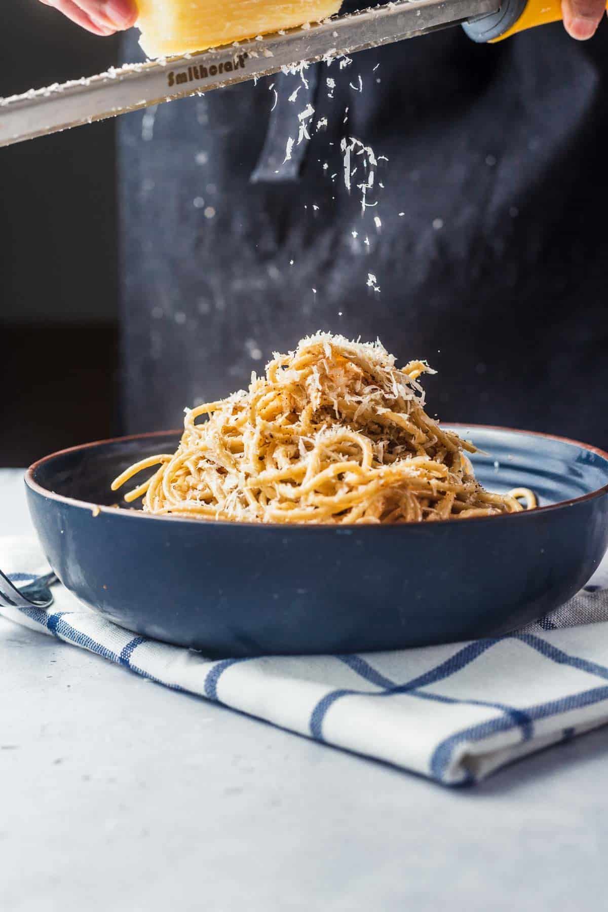 Szechuan Cacio e Pepe in a blue bowl with fresh parmesan cheese grated on top.