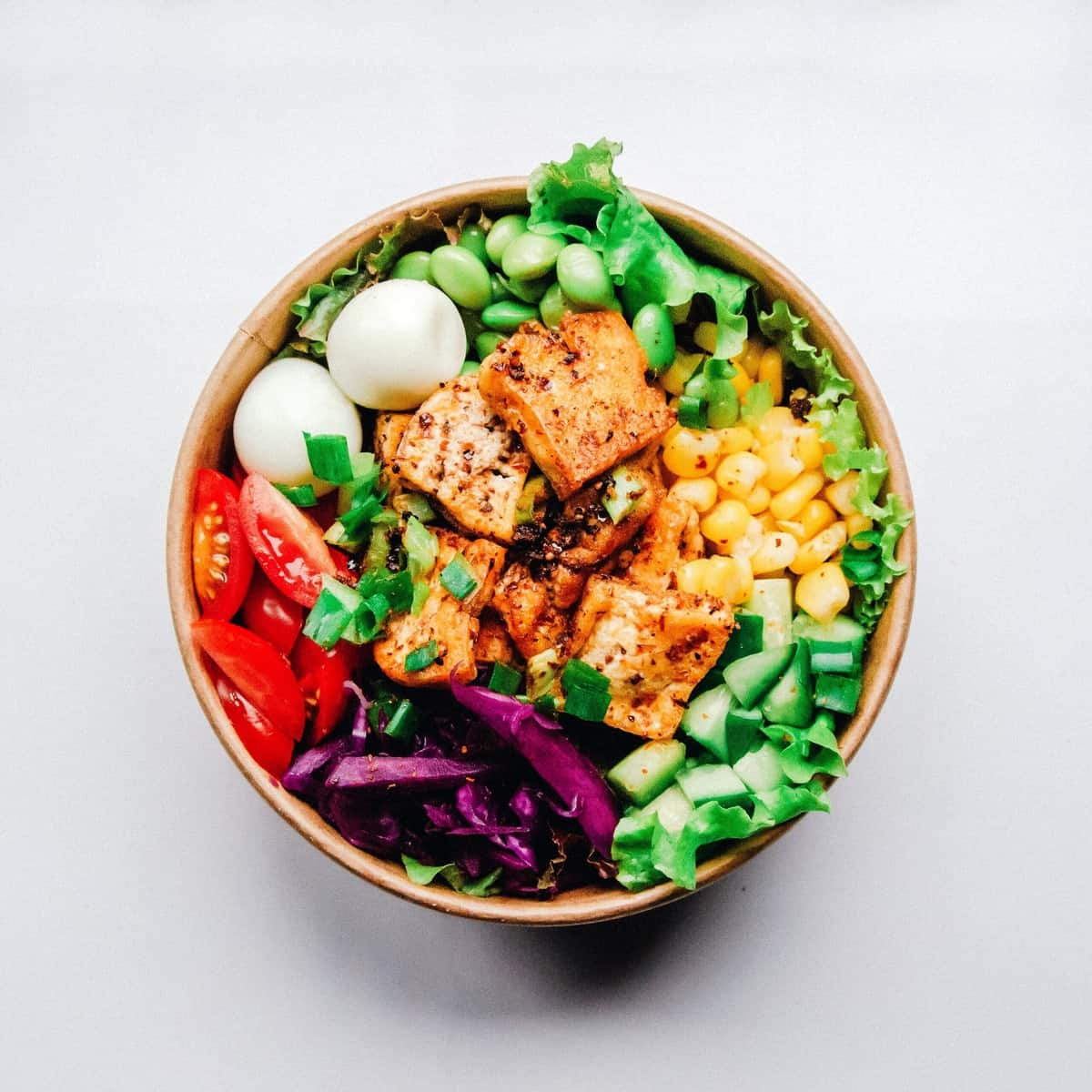 A close up of a tofu salad in a bowl with edamame, cucumber, tomato, corn, and cheese for those following the AB blood type diet.