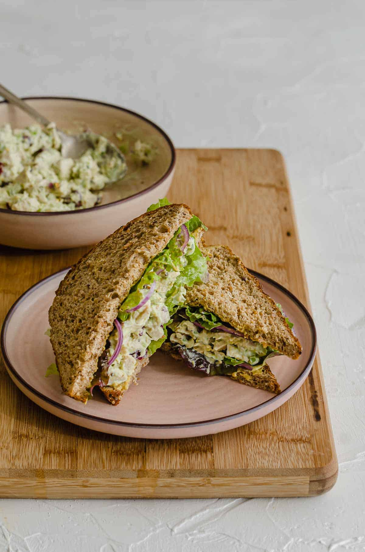 Close up of chicken salad sandwich on a pink plate.