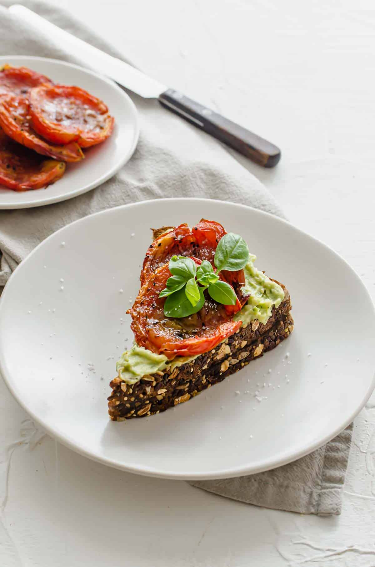 Close up of vegan avocado toast on a white plate topped with roasted tomato and a basil leaf with extra roasted tomatoes in the background.