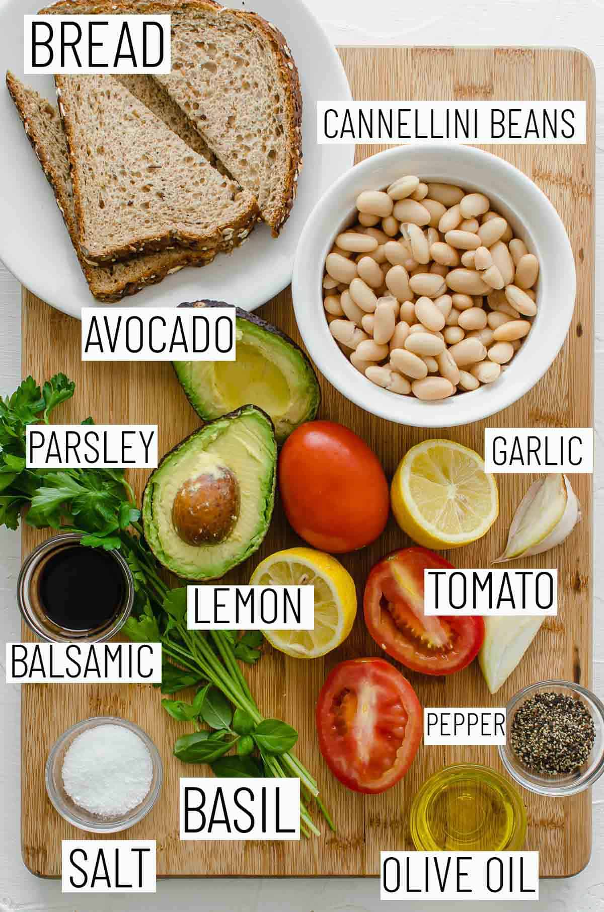 Flat lay image of recipe ingredients including lemon, pepper, Roma tomatos, olive oil, salt, basil, balsamic, parsley, white bean, avocado, and bread.