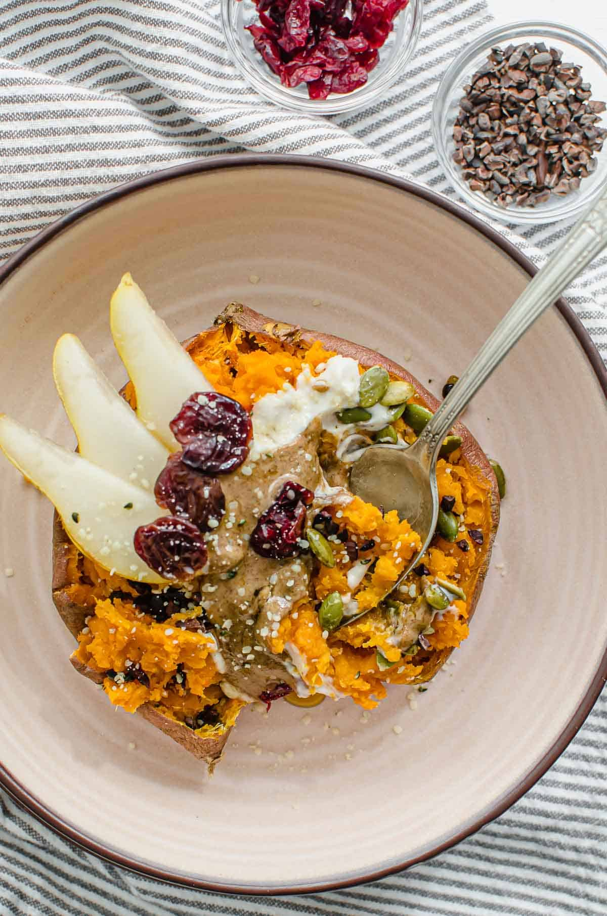 Birds eye view image of sweet potato breakfast bowl with cacao nibs and cranberries on the side.