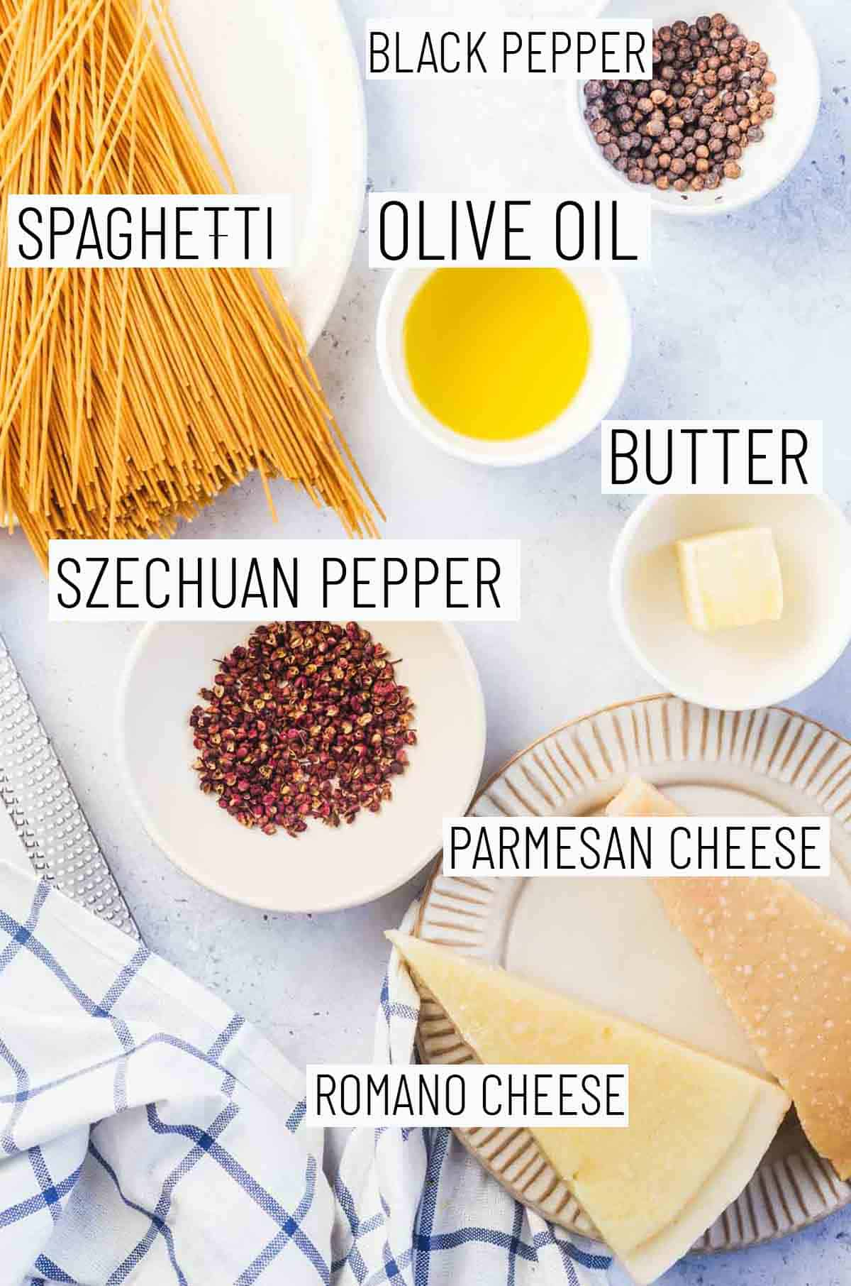 Flat lay image of recipe ingredients including black pepper, olive oil, butter, spaghetti, parmesan cheese, Romano cheese, and Szechuan pepper.
