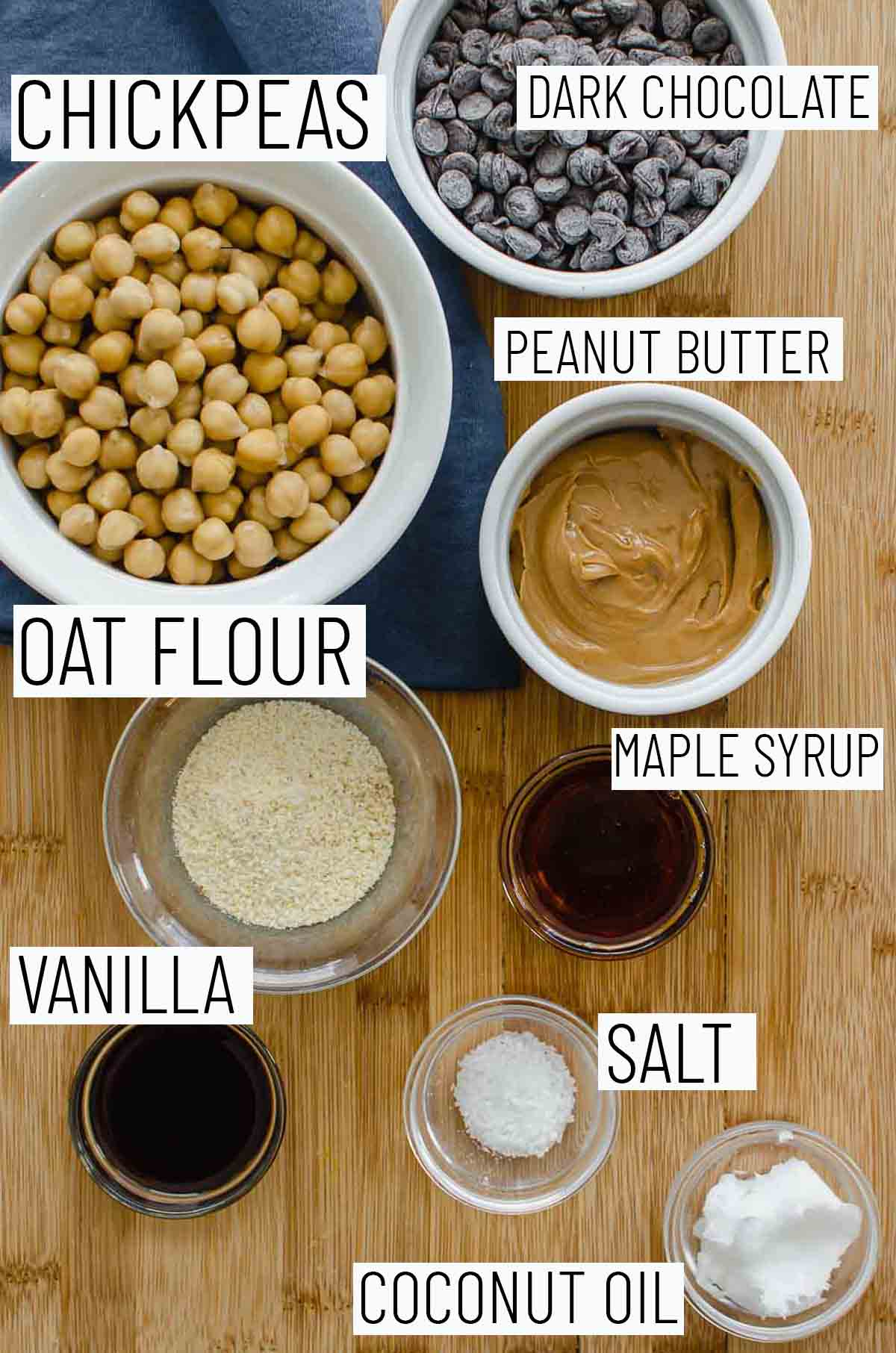 Flat lay image of recipe ingredients including maple syrup, peanut butter, oat flour, vanilla, coconut oil, salt, and chickpeas.
