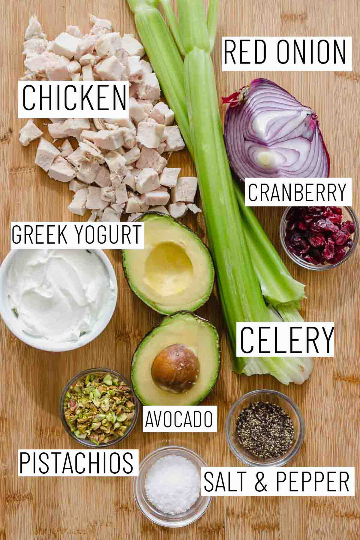 Flat lay image of portioned recipe ingredients including red onion, chicken, cranberry, Greek yogurt, celery, avocado, and pistachio.