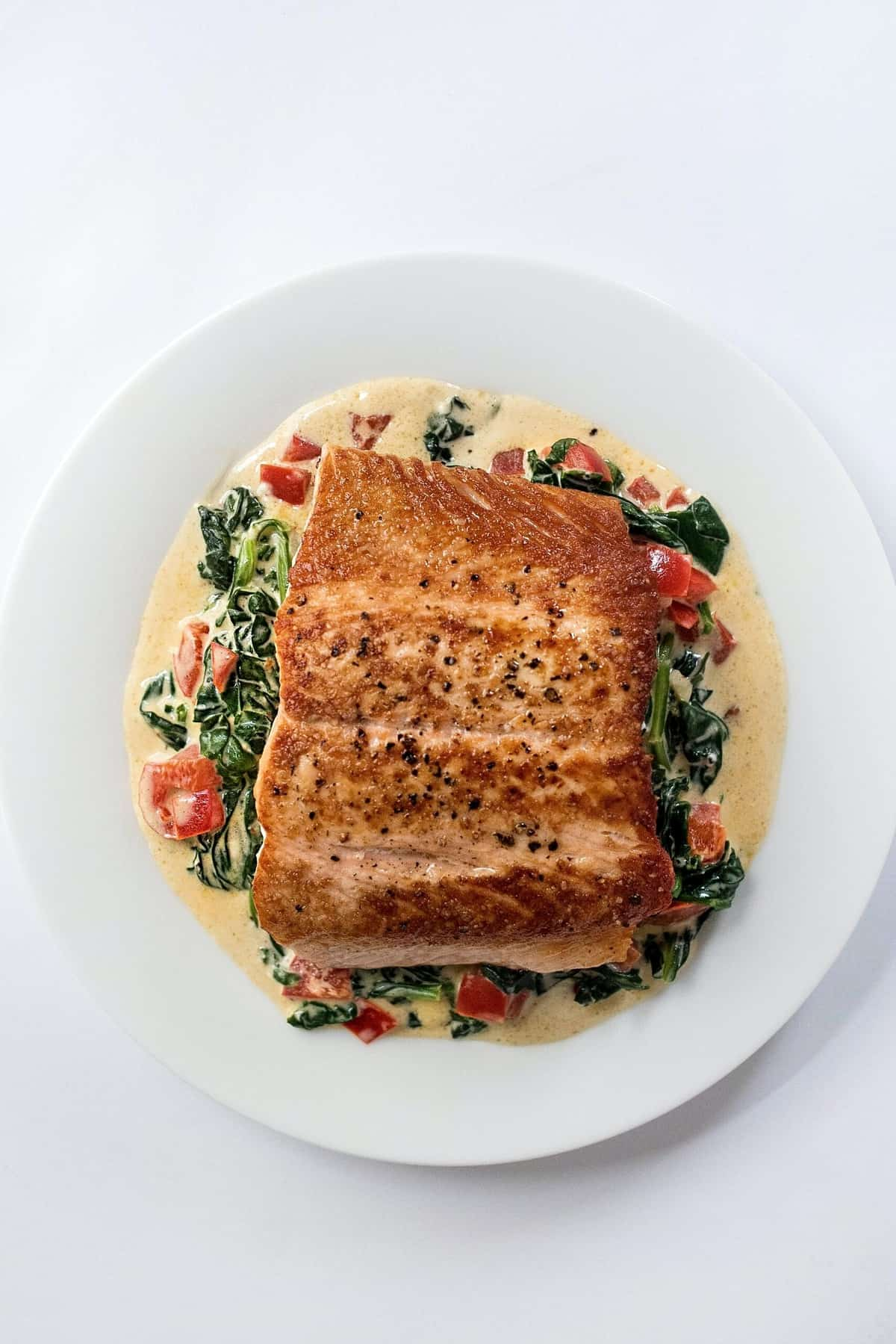 Birds eye view of salmon on a bed of greens in a white plate as an option for those following the type O blood type diet.