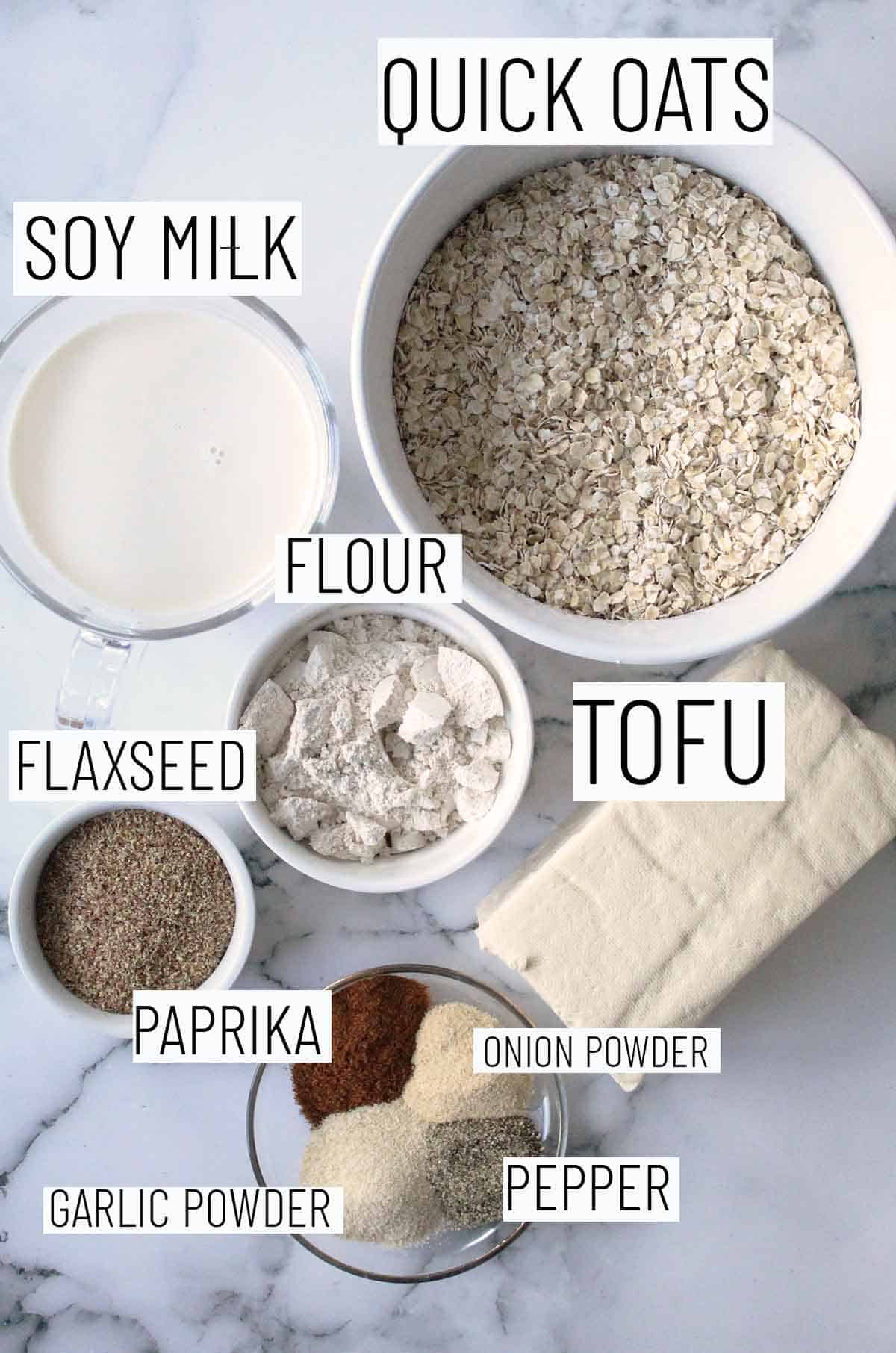 Flat lay image of recipe ingredients including oats, tofu, flour, soy milk, flaxseed, paprika, onion powder, garlic powder, and pepper.