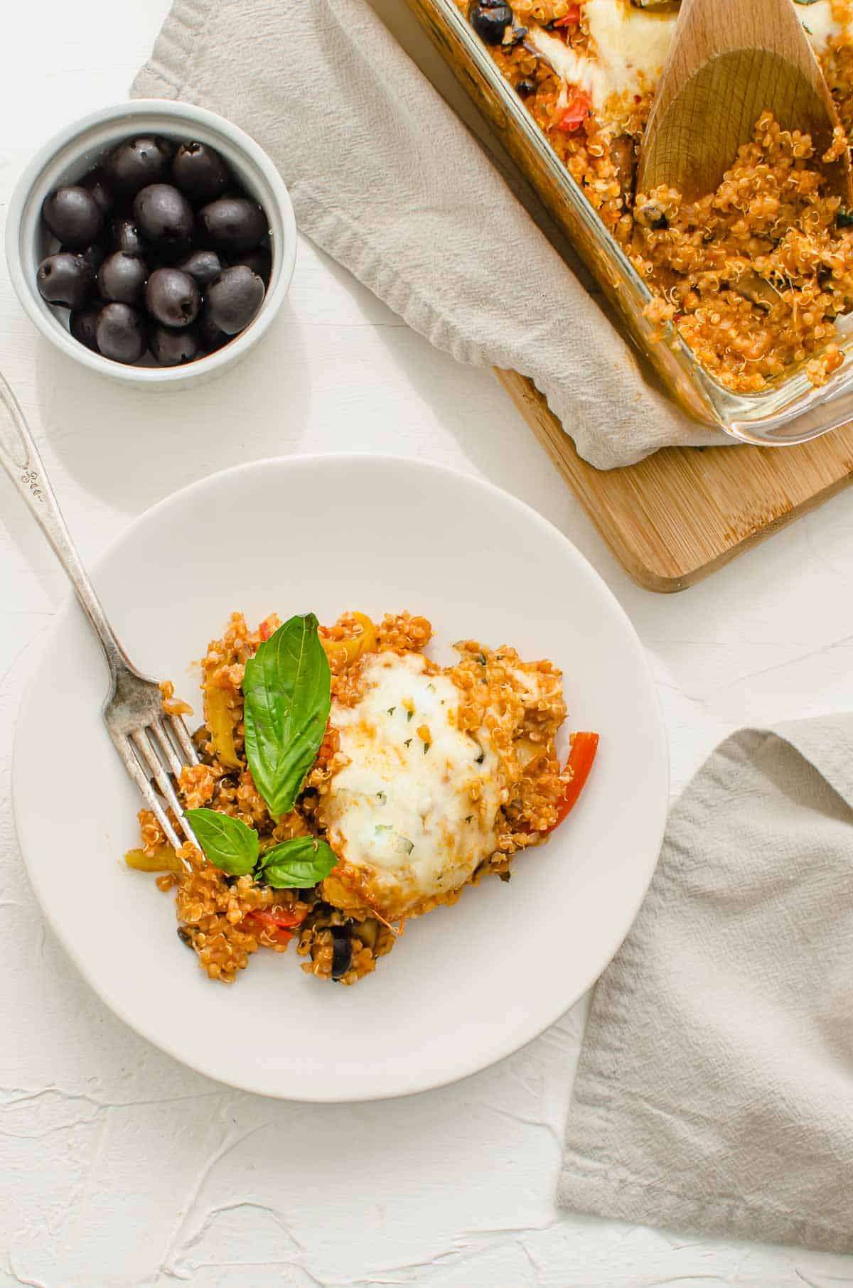 Birds eye view image of plated pizza quinoa casserole garnished with basil.