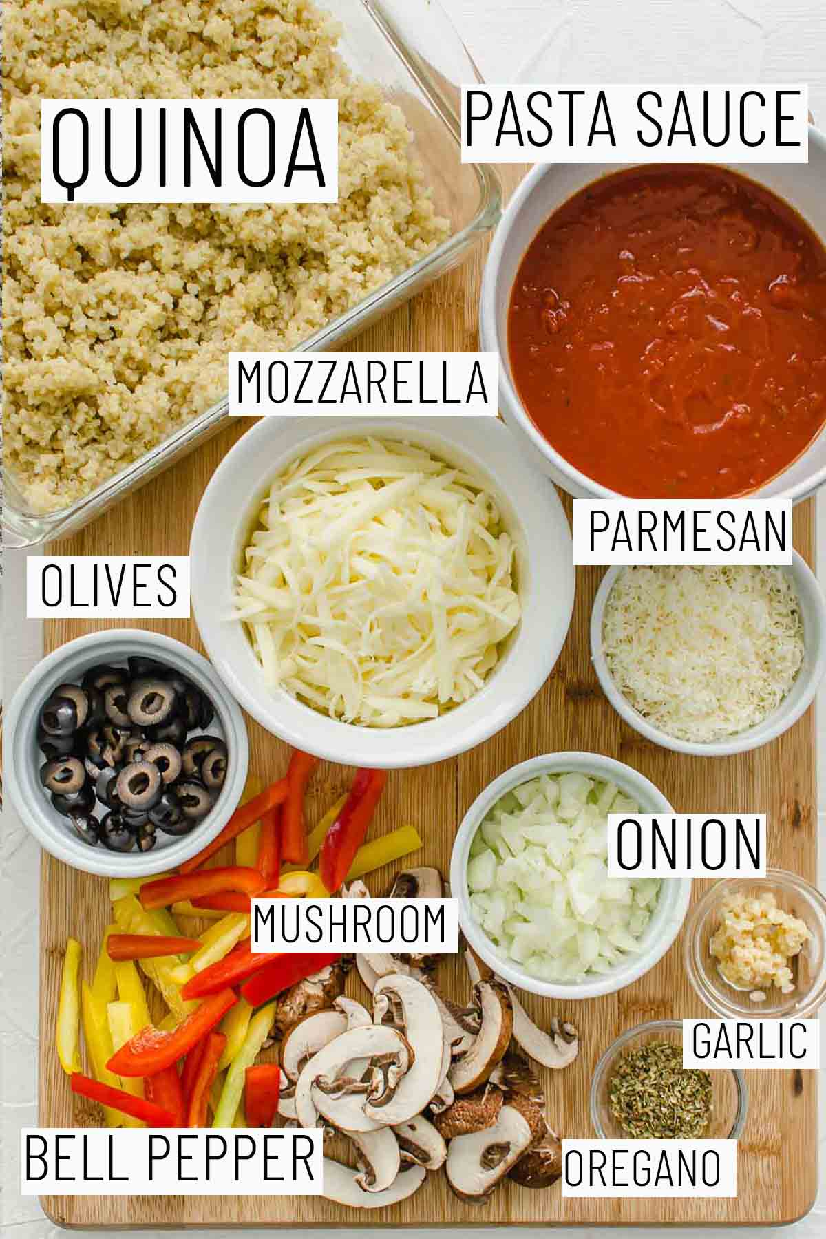 Flat lay image of portioned recipe ingredients including parmesan, mozzarella, olives, onion, garlic, oregano, bell pepper, quinoa, and pasta sauce.