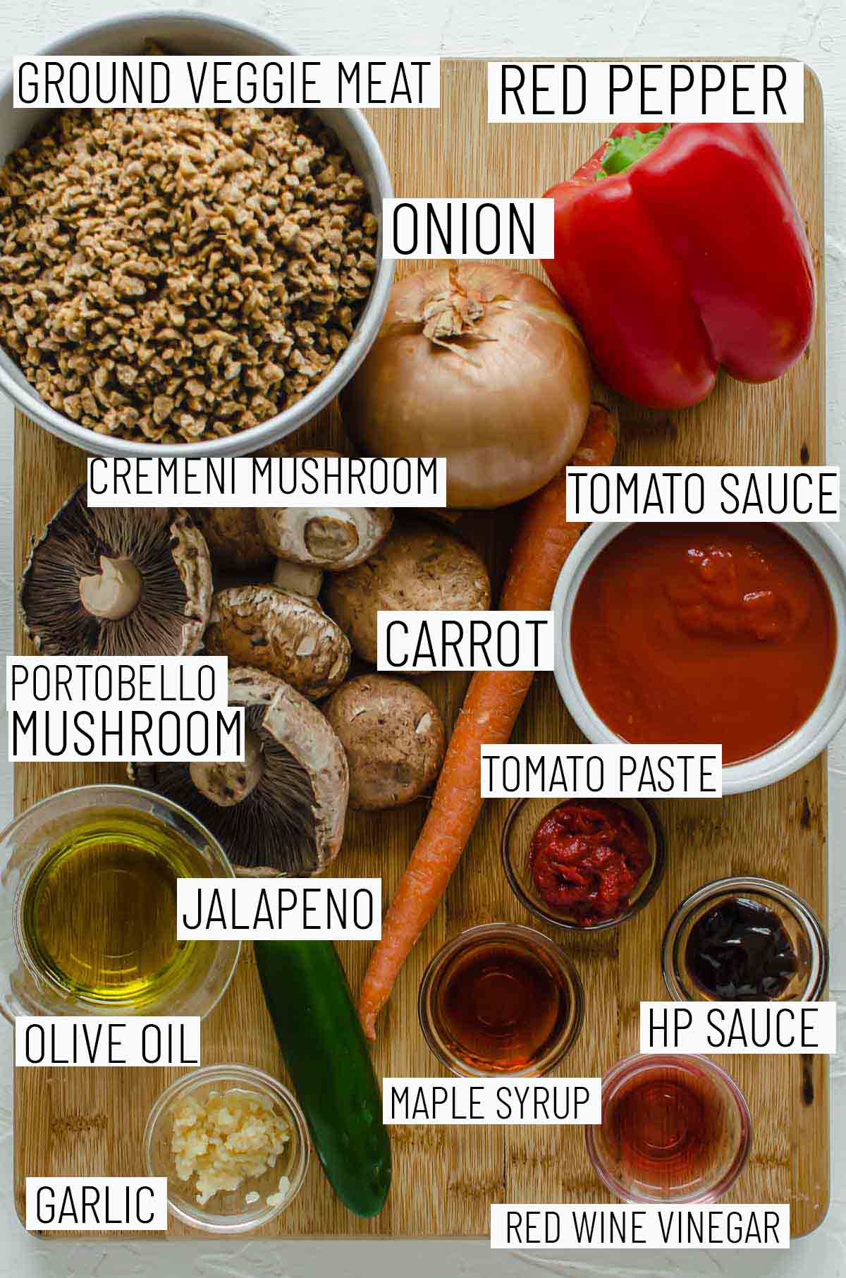 Flat lay image of portioned recipe ingredients including red pepper, onion, veggie meat, tomato sauce, mushrooms, tomato paste, jalapeno, olive oil, garlic, red wine vinegar, HP sauce, and maple syrup.