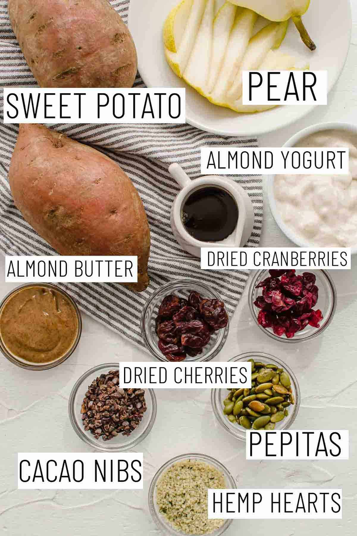 Flat lay image of portioned recipe ingredients including sweet potato, pear, almond yogurt, dried cranberries, almond butter, dried cherries, pepitas, cacao nibs, and hemp hearts.