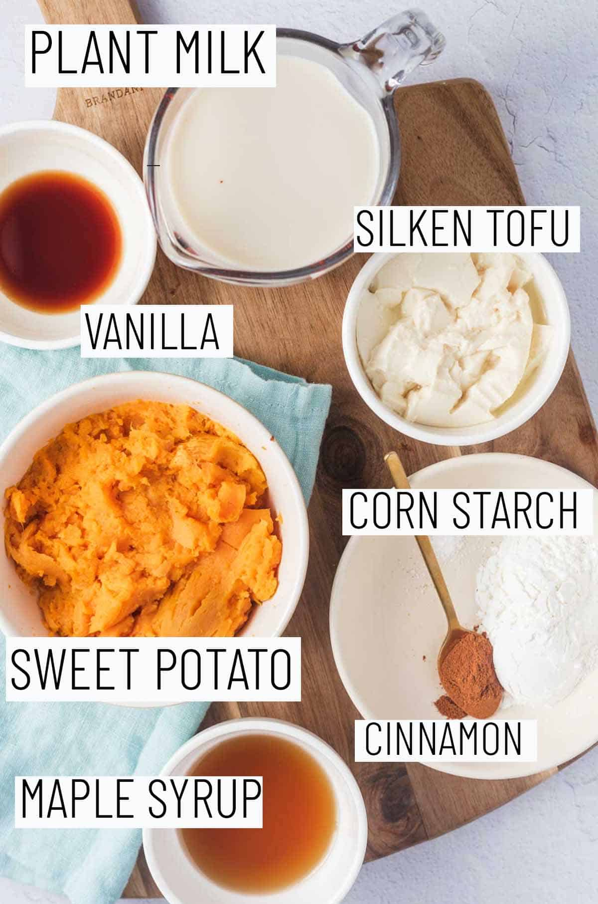 Flat lay image of portioned recipe ingredients including maple syrup, cinnamon, cornstarch, sweet potato, tofu, milk, and vanilla.