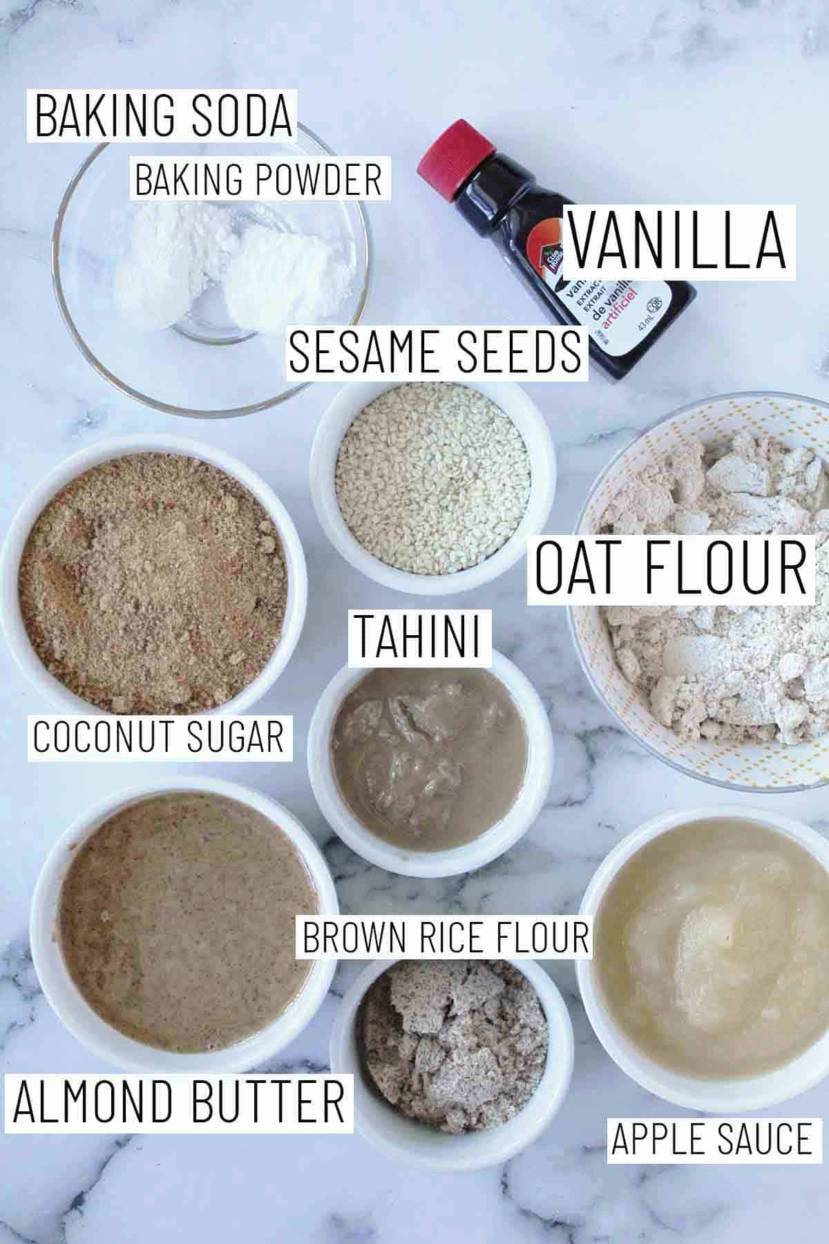 Flat lay image showing portioned recipe ingredients including oat flour, tahini, coconut sugar, brown rice flour, almond butter, apple sauce, vanilla, sesame seeds, baking soda, and baking powder.