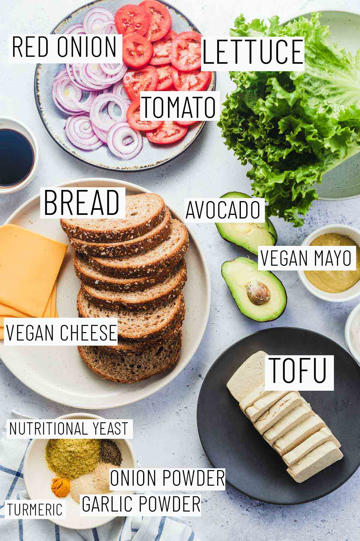 Flat lay image of portioned recipe ingredients including bread, cheese, mayo, tofu, lettuce, tomato, red onion, and seasonings.