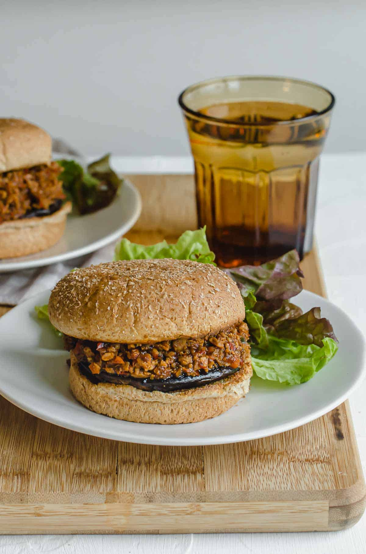 Close up of vegan sloppy joe on a white plate with a glass of water in the background.