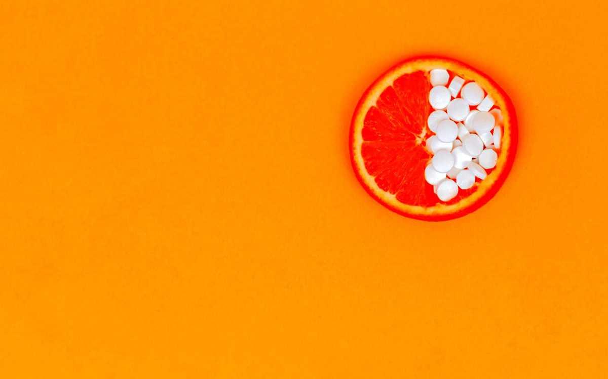 Collagen supplements on an orange slice.
