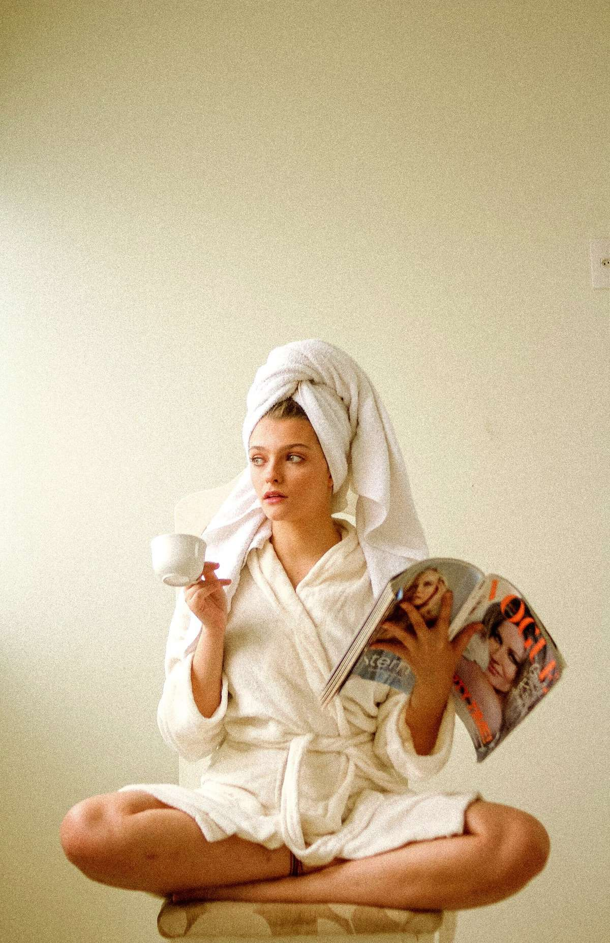 A woman in a robe, drinking coffee, and reading a magazine.