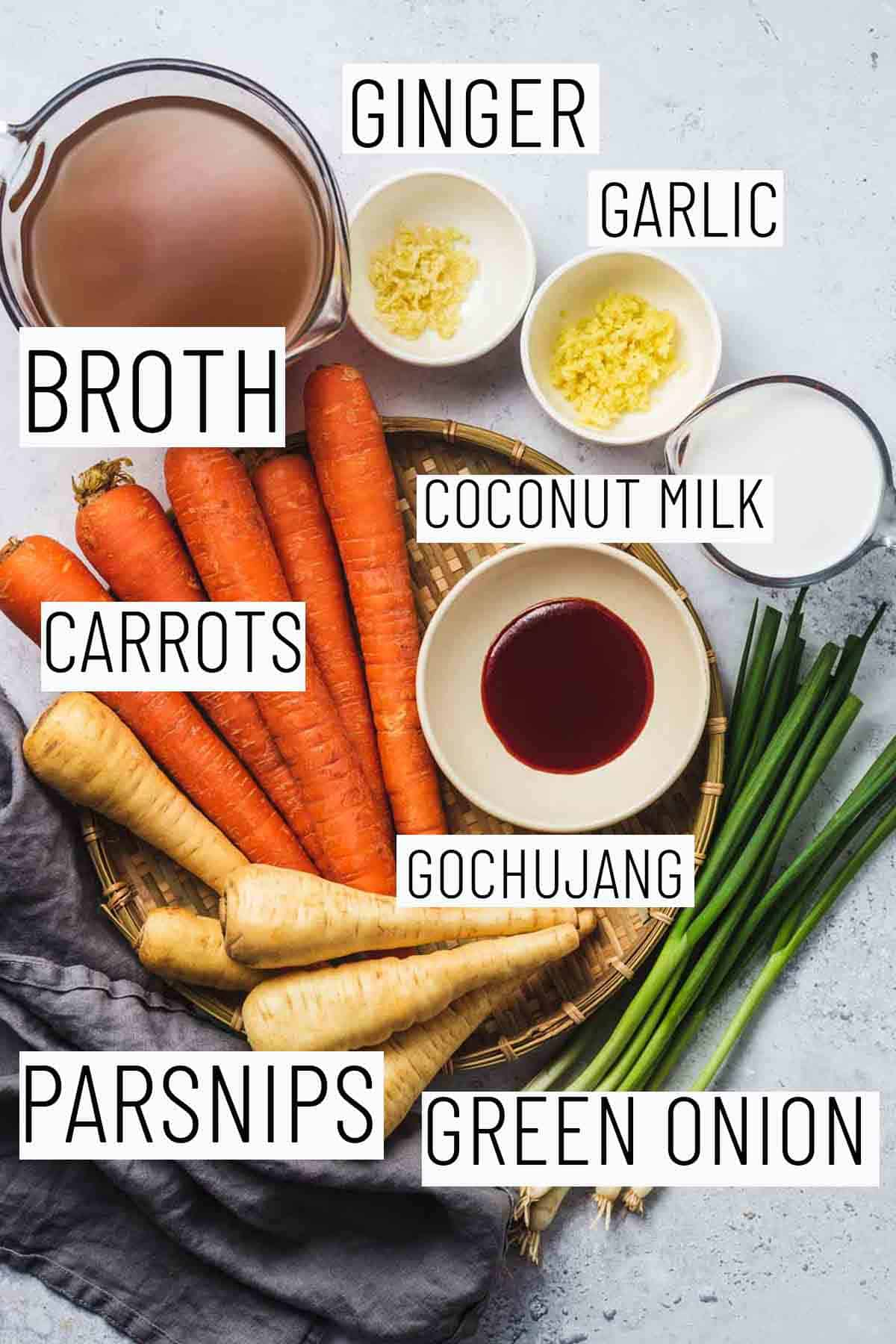 Flat lay image with portioned recipe ingredients including green onion, parsnips, Gochujang, garlic, ginger, broth, and coconut milk.