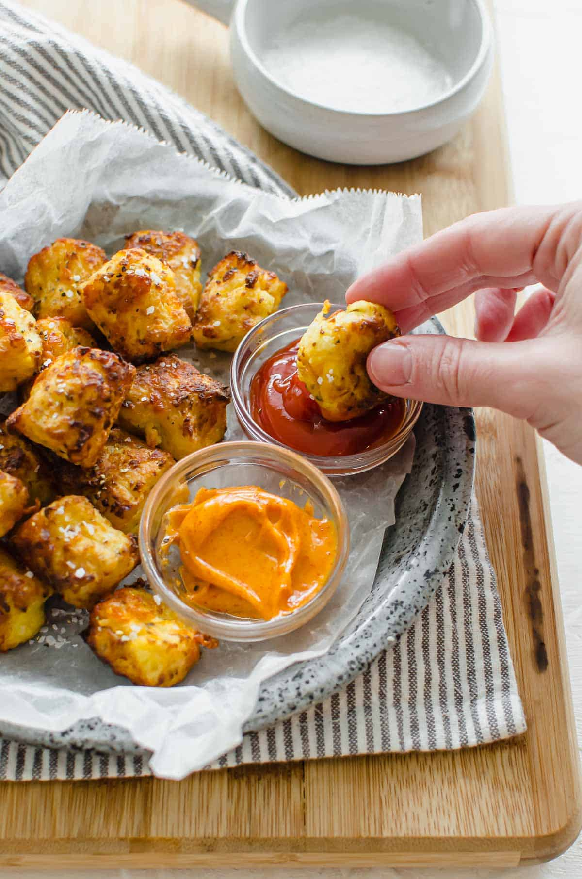 Close up of a hand dipping cauliflower tot in ketchup.