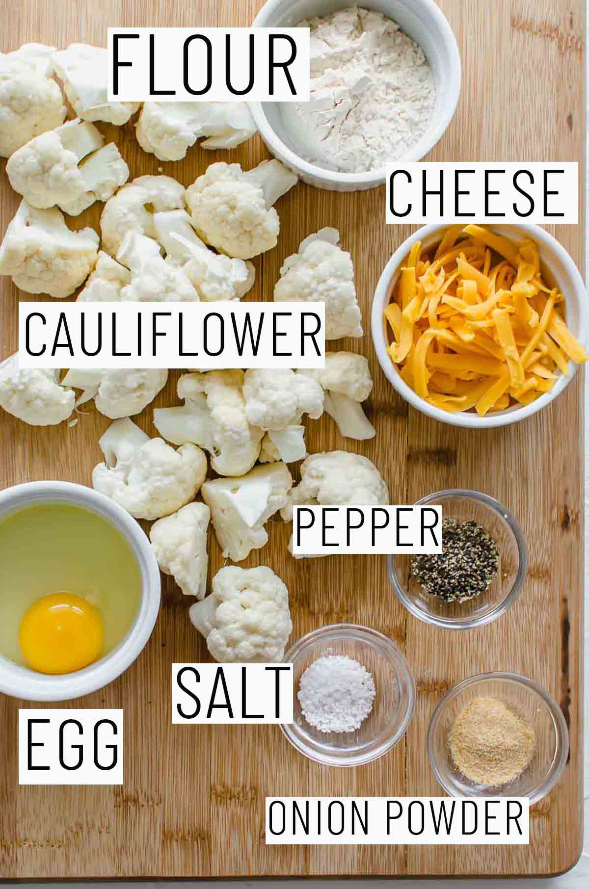 Flat lay image of recipe portioned ingredients including cauliflower, flour, egg, cheese, and seasonings.
