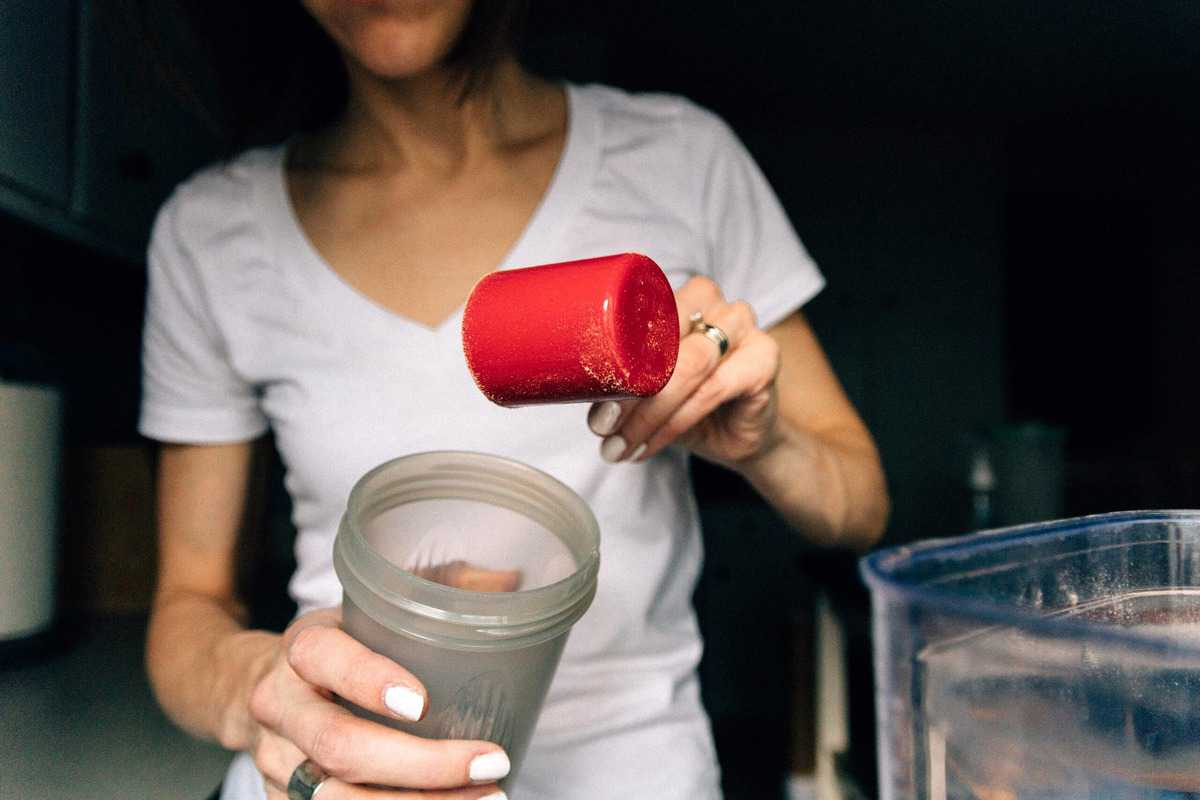 A women scooping supplement into a portable bottle.