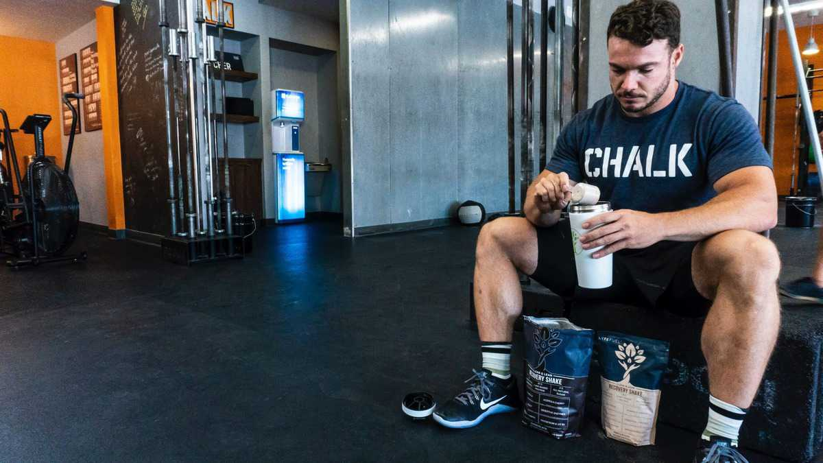 A man at the gym sitting on a bench and scooping protein powder into a tumbler mug.