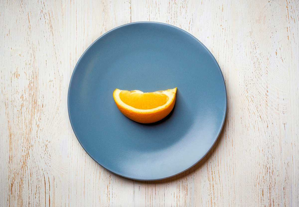 A single orange wedge on a blue plate to show how restrictive intuitive fasting is.