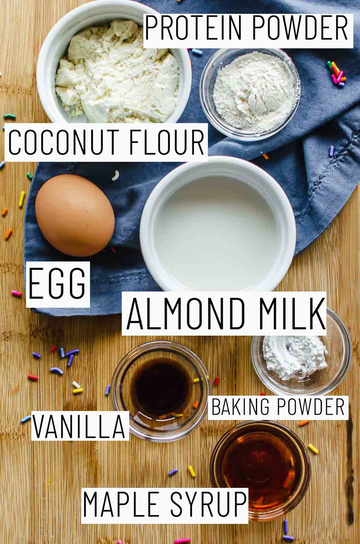 Flat lay image of portioned recipe ingredients including baking powder, maple syrup, vanilla, egg, coconut flour, and protein powder.