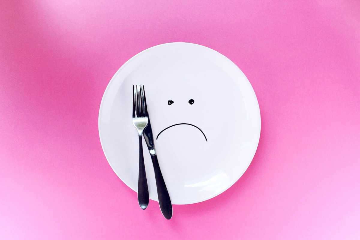 An empty plate with cutlery placed overtop to demonstrate how sad and restrictive intuitive fasting is.