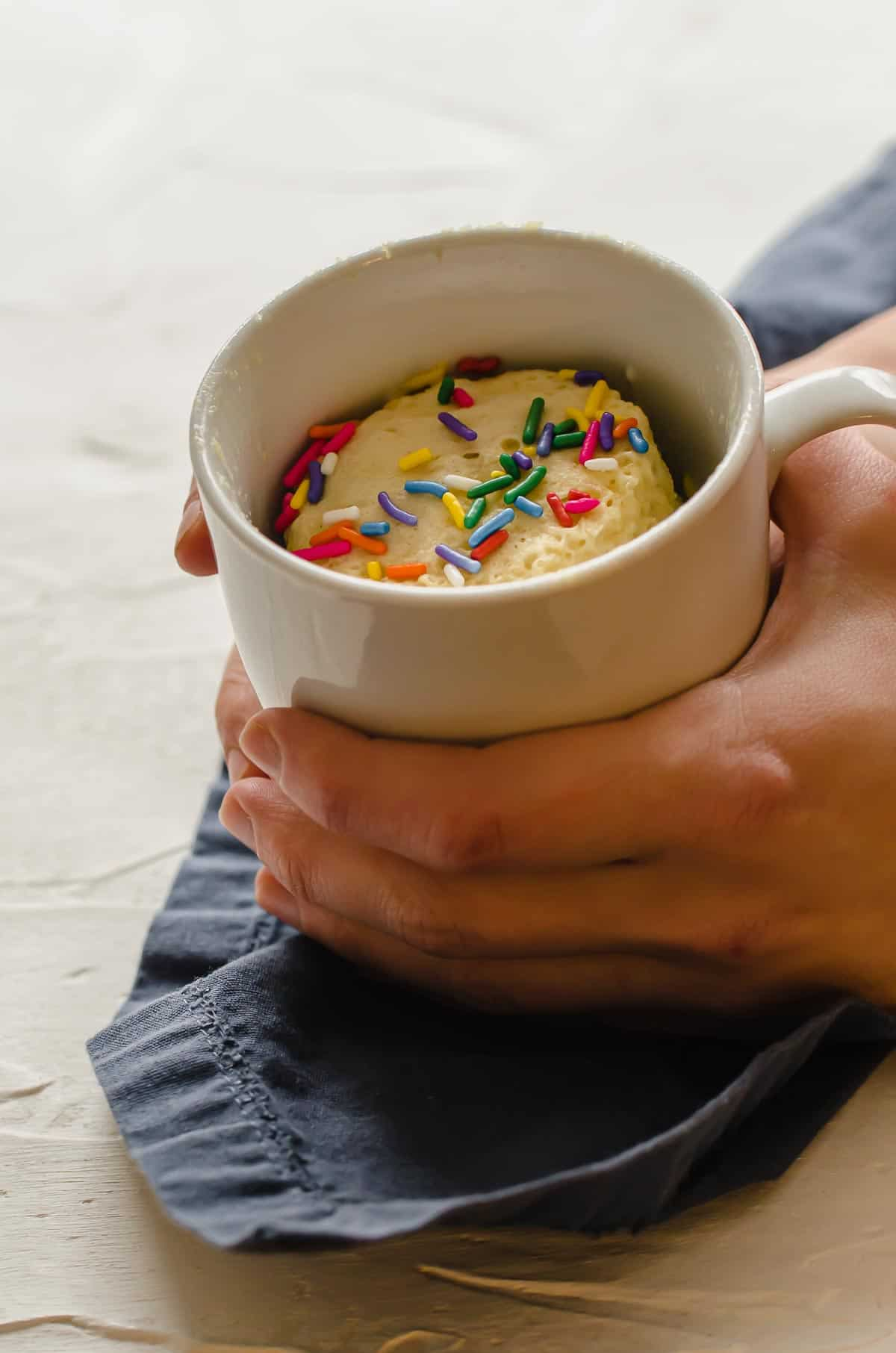 Two hands holding protein mug cake topped with sprinkles.