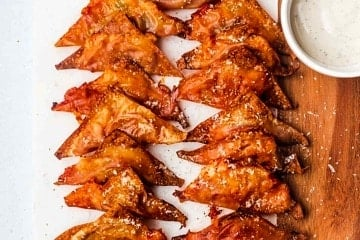 A serving board with multiple air fryer pizza rolls made with wonton wrappers.