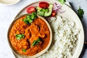 Overhead view of a plate of rice with a bowl of tofu butter chicken alongside garnishes.