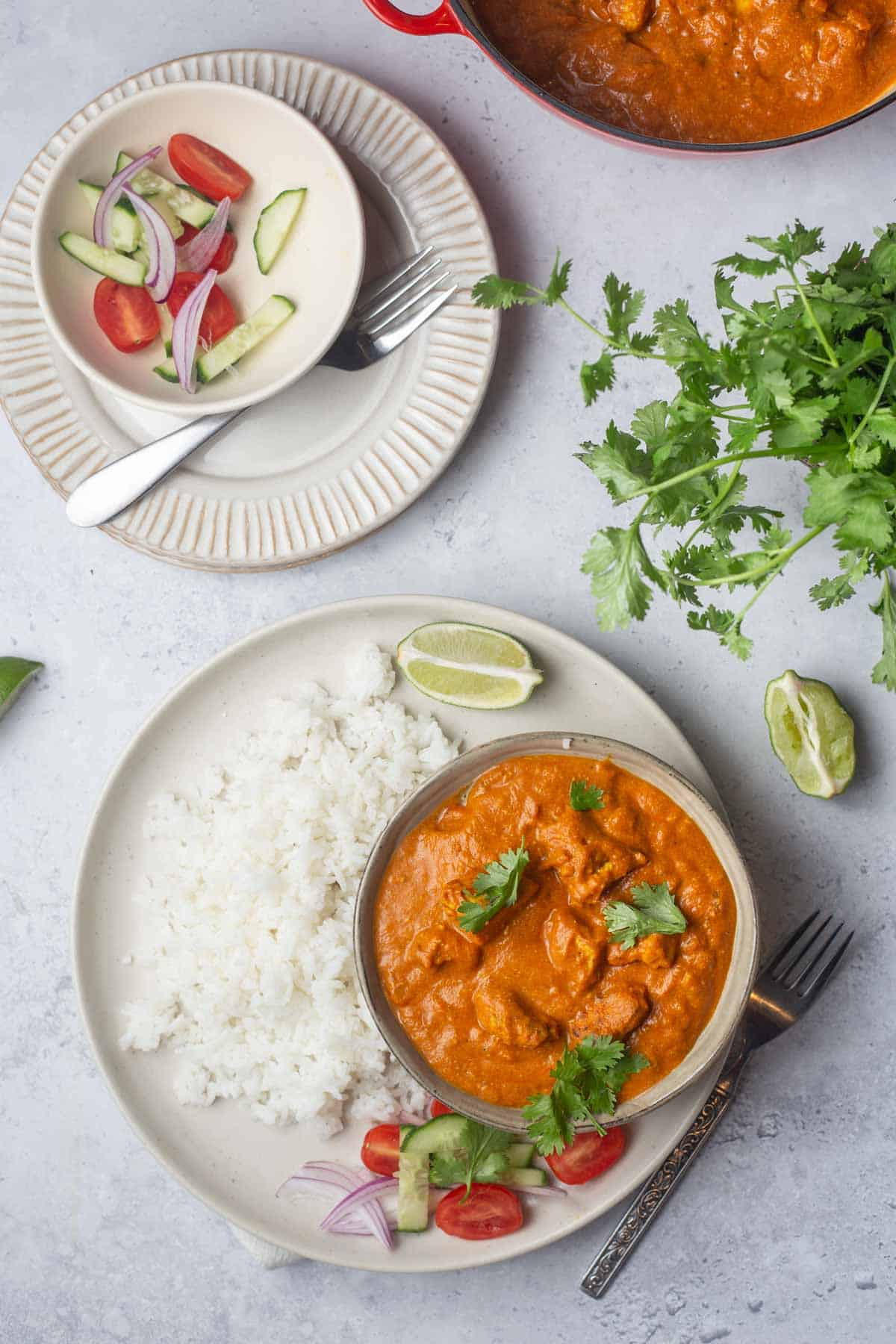 Overhead view of a bowl of butter chicken with a plate of rice beside it with a small bowl of garnish nearby.