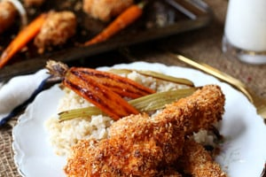 Pinterest graphic of a plate of buffalo chicken strips with grains, carrots, and celery.