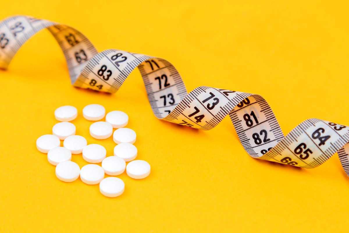 Several Arbonne supplements beside a measuring tape.