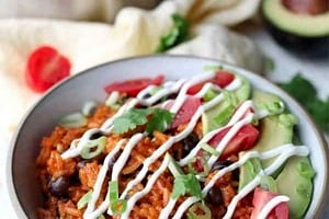 Pinterest graphic of an enchilada bowl with sour cream and garnishes.