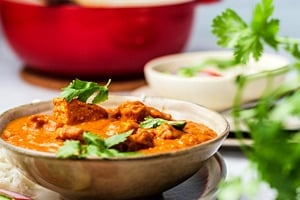 Pinterest graphic of a side profile view of a bowl of vegan butter chicken with a large pot in the background.