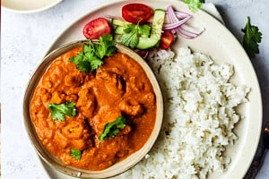 Pinterest graphic of the overhead view of a bowl of butter chicken with tofu and a side of rice.