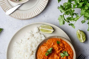 Pinterest graphic of a plate of rice with a bowl of vegan butter chicken.