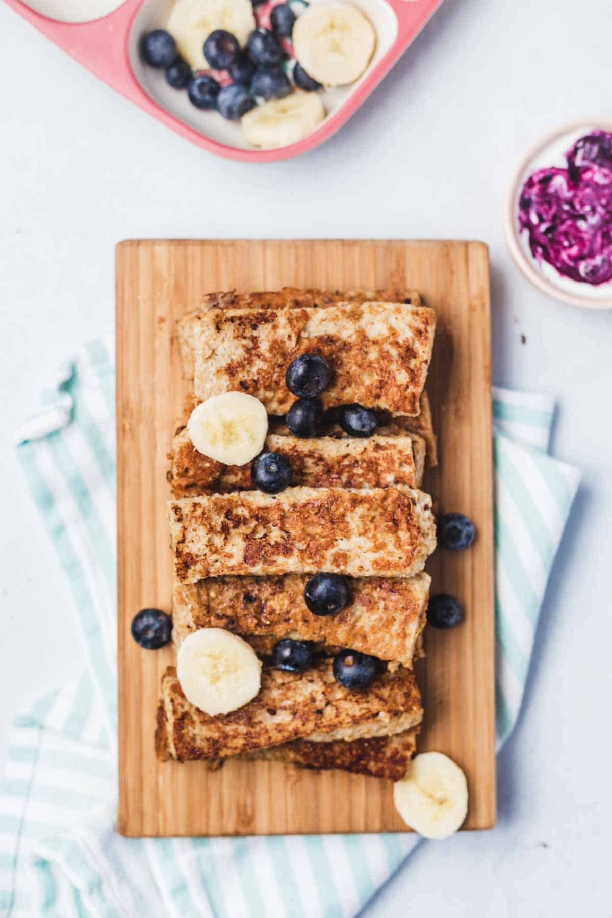 Overhead view of a serving board with a stack of French toast sticks.