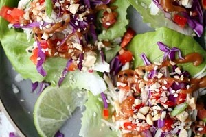 """Pinterest graphic of a plate of three chicken lettuce wraps with the text overlay """"no-cook chicken lettuce wraps."""""""