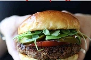 """Pinterest graphic of a hand holding a quinoa burger with the text overlay """"quinoa burger with walnuts."""""""