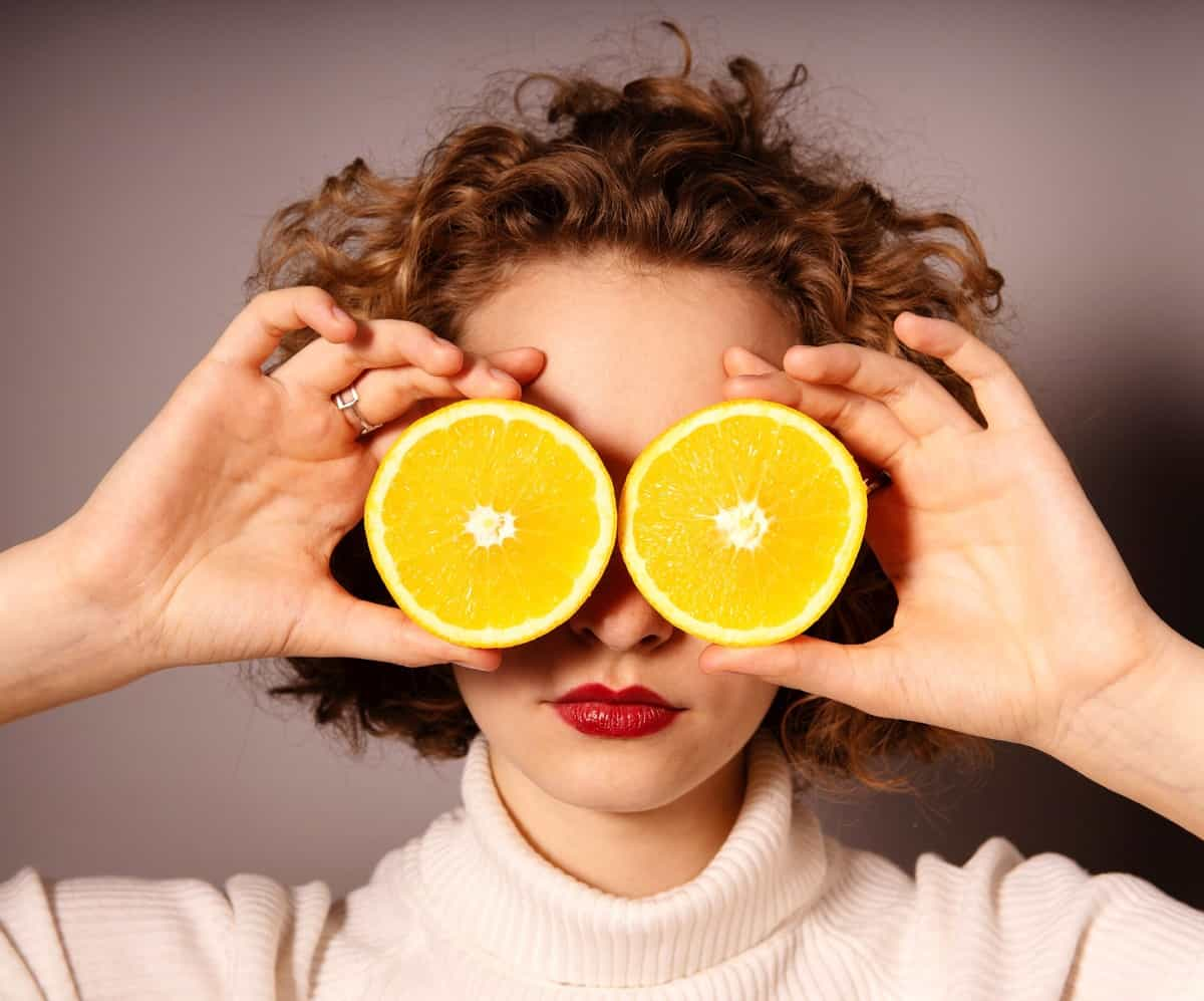 Woman holding up two orange slices up to her eyes.