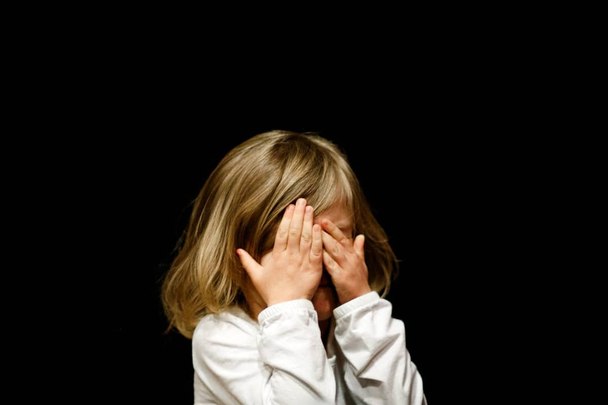 Crying little girl covering her face with her hands.