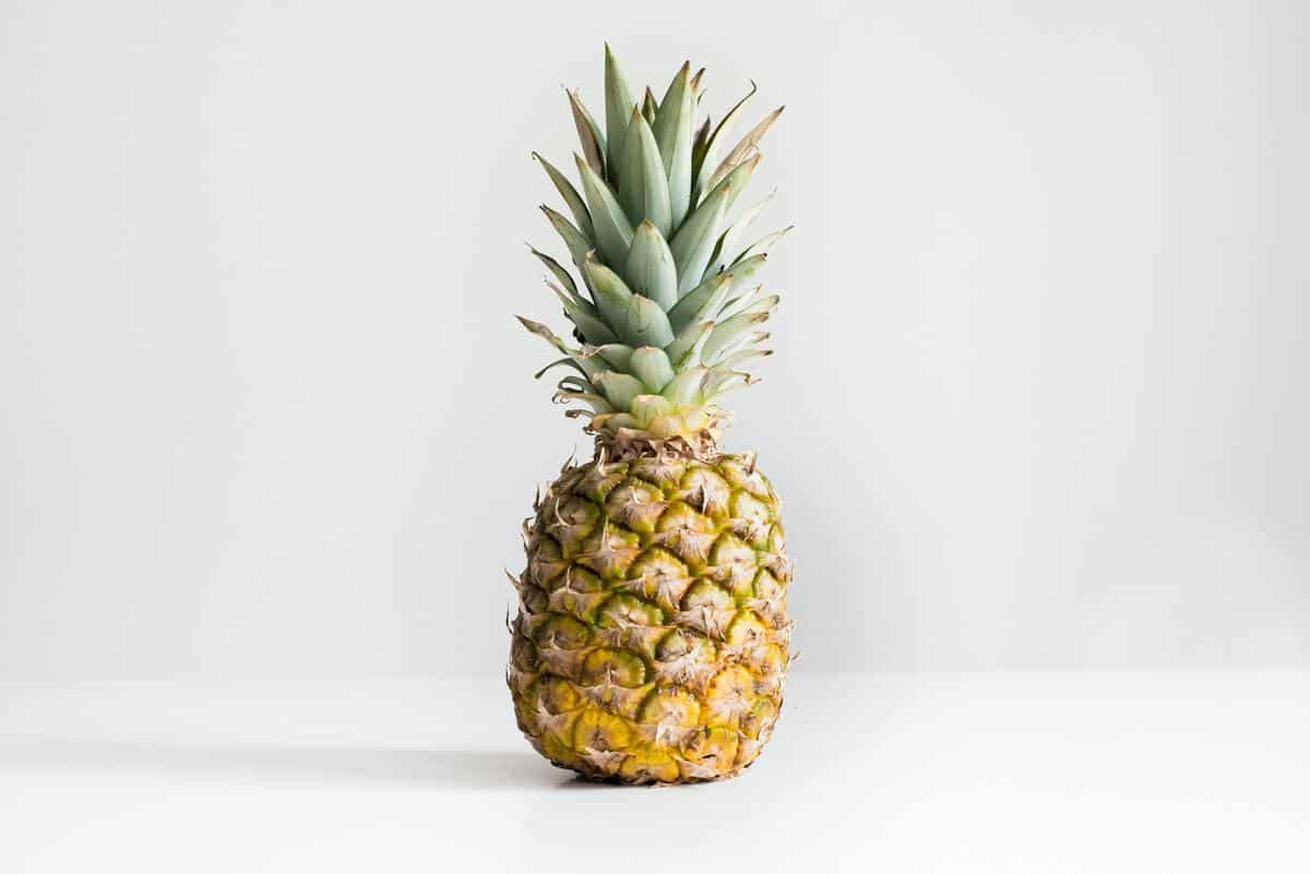 A pineapple on a white counter.