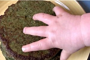 """Pinterest graphic of a toddler's hand reaching for the plate of pancakes with text overlay """"Baby Led Weaning Green Pancakes Made with Avocado and Spinach."""""""
