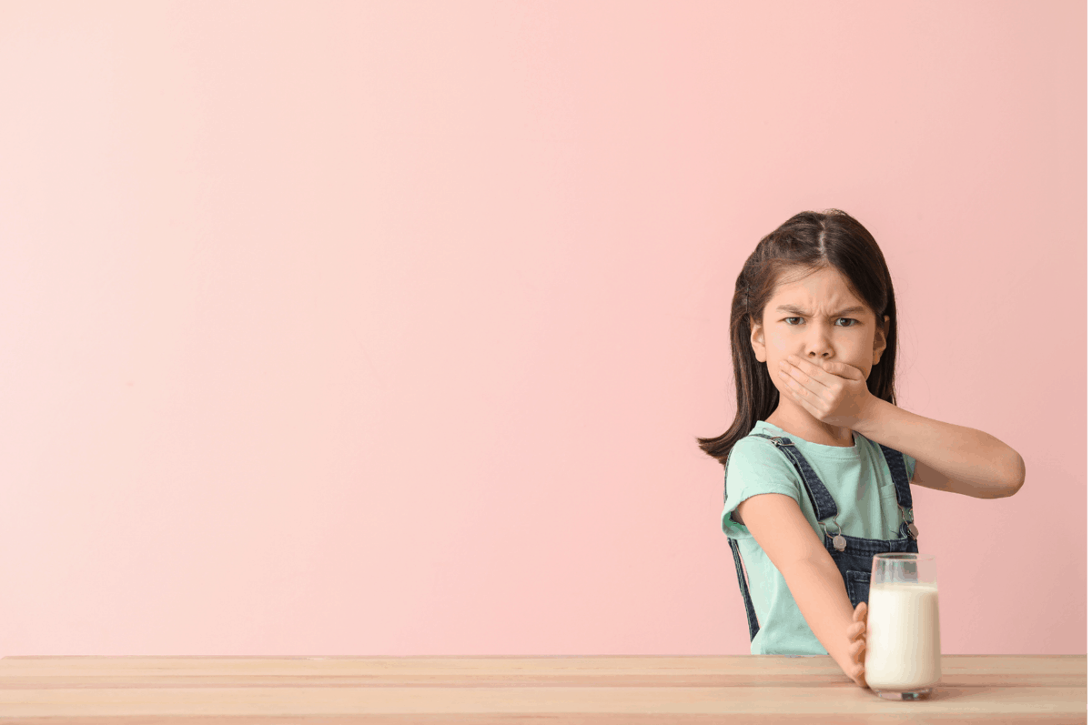 Young girl holding glass of milk and mouth.