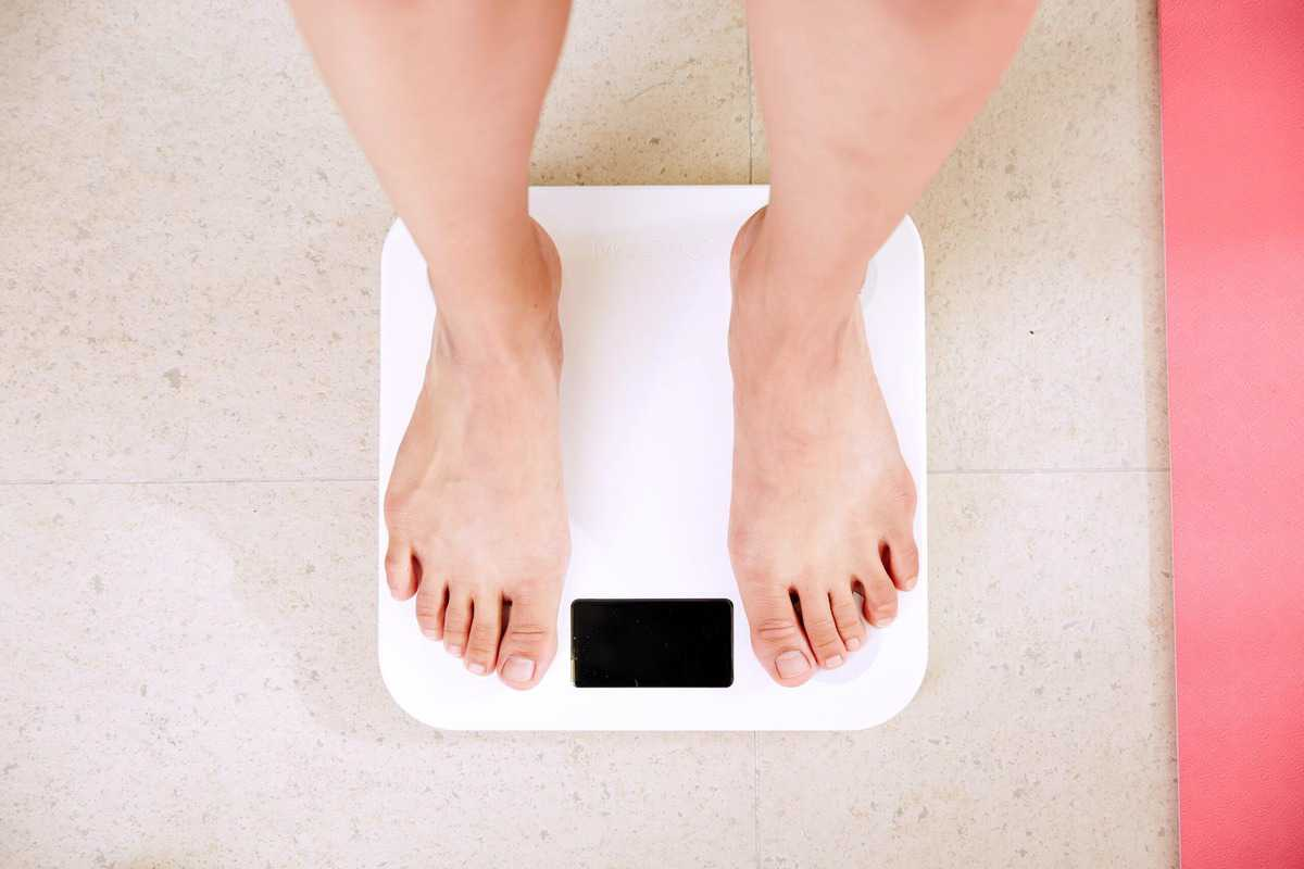 A person standing on a scale to assess weight loss.